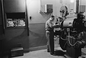 Man working with a projector in a movie theater
