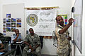 Mauritanian air force Sgt. Chief Bouha Khayri, right, an aircraft mechanic, discusses a bird and wildlife aircraft strike hazard scenario with U.S. Air Force Master Sgt. Jerome Williams, center, a ground safety 140902-F-FV908-002.jpg