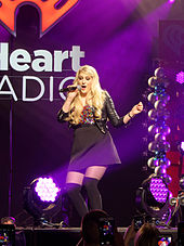 A young long-haired blonde woman singing into a microphone onstage. She wears a black skirt and jacket while pink stage lighting shines upon her.