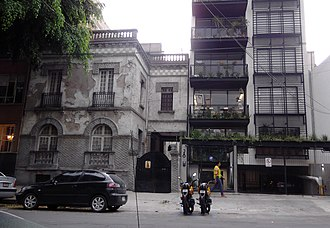 Gentrification - Early 20th-century damaged buildings next to a new loft tower in Mexico City's Colonia Roma