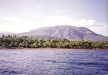 Image of a volcano that steadily rises over the horizon in the background. In the foreground is a sea, and in the middleground is a large swath of mangrove and other jungle trees.