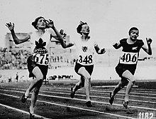 Myrtle Cook of Canada (left) winning a preliminary heat in the womens 100 metres race at the VIIIth Summer Olympic Games.jpg