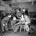 Nederlandse militairen rond een collega met kerstmanmasker die een sigaret rookt, Bestanddeelnr 255-9414.jpg