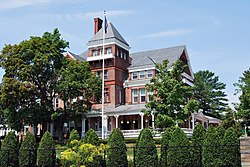 An ornate brick house with a pyramid-roofed tower on the front seen from slightly below. In front is a flagpole and some tall trees, with shrubbery and a chain link fence at the bottom of the image, closer to the camera.