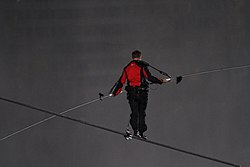 A man in black and red on a tightrope