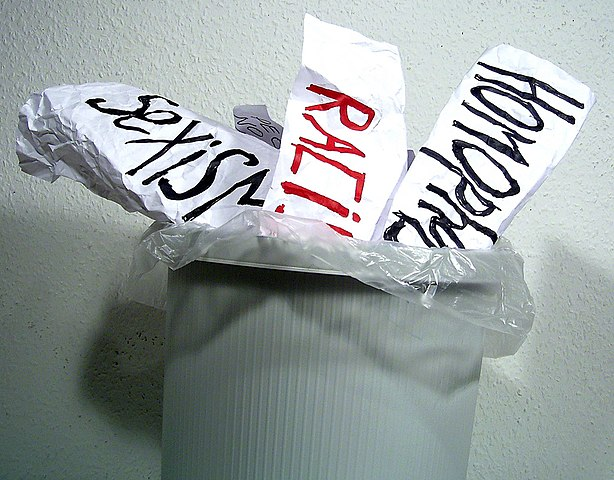 "Three crumpled paper signs that read ""sexism, racism, and homophobia"" sticking out of a trash can"