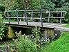 foto van De brug over de wegsloot bestaat uit twee betonnen landhoofden die over de sloot met elkaar zijn verbonden door een samenstelsel van houten planken. Hierop zijn aan de buitenzijden onder een schuine hoek twee relingen geplaatst, opgebouwd uit houten stijlen en twee rijen ijzeren regels