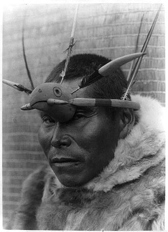 Yupik - A Nunivak Cup'ig man with raven maskette. The raven (Cup'ig tulukarug) is Ellam Cua or Creator god in the Cup'ig mythology
