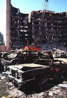 Several fire-damaged cars located in front of a partially destroyed multi-story building.