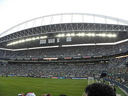 The grandstand of a stadium filled with people. The stadium has distinctive trusses for support.