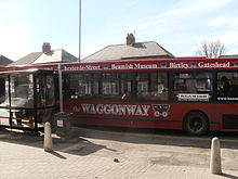 "In a sunlit suburban street, a single-decker red bus is parked at a bus stop facing left. Above its windows are the words ""Waggonway"", ""Chester-le-Street"", ""Beamish Museum"", ""Birtley"" and ""Gateshead"". On a large window on the right is the word ""Beamish"", and below the windows are the words ""the Waggonway"" and a stylised picture of an early railway cart."