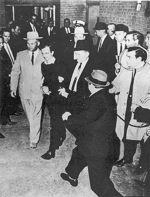 Jack Ruby, just a split-second before firing one shot into Oswald, who is being escorted by police detectives Jim Leavelle (tan suit) and L.C. Graves for the transfer from the City Jail to the Dallas County Jail. - Assassination of John F. Kennedy