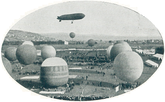 An airship floating behind a number of balloons in the foreground.