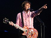 McCartney points to the audience while performing on stage.