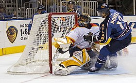 An ice hockey player wearing a blue jersey following through on a shot against a goaltender wearing a white jersey from close proximity. The goaltender's left blocker and pad are outstretched as he watches the puck go in the net behind him.
