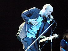 A middle-aged Caucasian man in a blue pin stripe suit with a shaved head sings into a microphone and smiles.