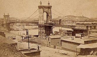 "John A. Roebling Suspension Bridge - Carte de visite of the ""Suspension Bridge Cincinnati"" (from a stamp on the back), taken from Covington looking toward Cincinnati, ca. 1870"