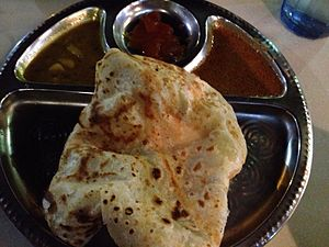 Roti canai - Roti canai with two curries on a stainless steel thali.
