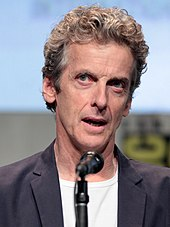 Peter Capaldi seated with microphone