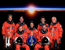 John Glenn and the rest of the STS-95 crew dressed in their bright orange spacesuits for their official portrait, with a sunset from space in the background