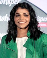 A photograph of a young woman wearing green coloured jacket.