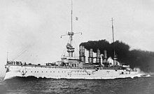 A large white warship with gray superstructure; several men are standing on the bow
