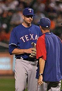 Tall player engaged in a mound conference with shorter man