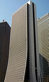 Ground-level view of a thin, white high-rise; the two wider sides curve and flair out at the bottom