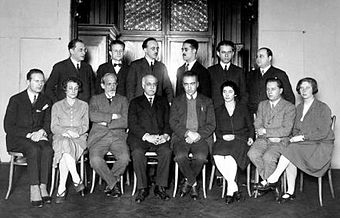 monochrome photograph of eight seated people, with a row of six people standing behind them
