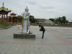 Elista - A Kalmyk lady praying in front of the statue before entering the temple