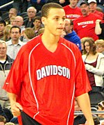 "A young man in his early 20s is warming up for a basketball game. He is wearing a red warm-up jersey with ""Davidson"" written in white across the chest. He is a light-skinned male of mixed race (half white by his mother, half African American by his father)."
