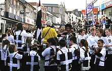 A street lined with shops is filled with hundreds of people. In the foreground are children wearing black vests each one defaced with a large white cross, the children surround a fiddler. In the background are spectators.