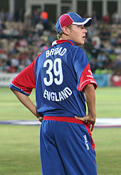 An English cricketer facing away and to the right, he is wearing the red, white and blue uniform of the England cricket team and he has his hands on his hips. The word BROAD appears above the number 39 and above the word ENGLAND on the back of his shirt.