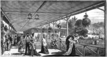 Black and white woodcut of men and women in Victorian dress on a long verandah. In the background are a large building attached to the verandah and a lake with boats on it.