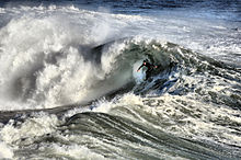 Photo showing surfer inside the curl of a breaking wave in turbulent waters