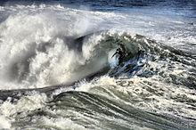 Foto che mostra surfer all'interno del ricciolo di un'onda di rottura in acque turbolente