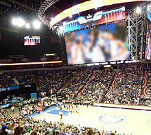 Photo from above the court showing large Daktronics scoreboard dominating the room, with Maya Moore's ponytail and Renee Montgomery visible on the video display. They were standing near the bench, not on the court at the time.