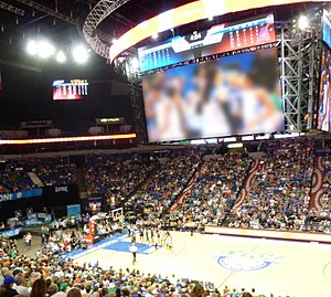 Photo from above the court showing large Daktronics scoreboard dominating the room, with Maya Moore's ponytail and Renee Montgomery on the video display and Sylvia Fowles, Natasha Howard and Jia Perkins visible at left. They were standing near the bench, not on the court at the time.