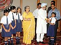 The school children tying 'Rakhi' to the Prime Minister, Dr. Manmohan Singh, on the occasion of 'Raksha Bandhan', in New Delhi on August 13, 2011. Smt. Gursharan Kaur is also seen (2).jpg