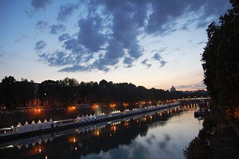 The Tiber River at the twilight with the St. Peter's Basilica behind.