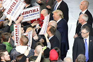 "Silent majority - Donald Trump and supporters attend a rally in Muscatine, Iowa in January 2016. Multiple supporters hold up signs, which read ""The silent majority stands with Trump""."