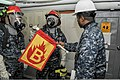 U.S. Navy Chief Logistics Specialist Damon Hankins, right, a damage control training team senior enlisted leader, evaluates the knowledge of Sailors on a hose team during a fire drill aboard the aircraft carrier 131115-N-XP477-039.jpg