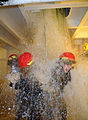 U.S. Navy Petty Officer 1st Class Korrin Cook and Petty Officer 2nd Class Asia Joyce are drenched by water flooding through an open hatch at the Damage Control School wet trainer at Naval Station Great Lakes 090114-N-IK959-145.jpg