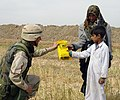 US Navy 030412-A-0000C-001 U.S. Army Lt. Col. Randy Stagner gives two Iraqi children a Humanitarian Daily Ration meal near the city of Najaf.jpg