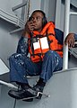 US Navy 040609-N-5313A-023 Seaman Kedric Young relays a message to a life raft coxswain during a Search and Rescue drill.jpg