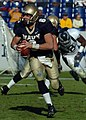 US Navy 041023-N-9693M-012 U.S. Naval Academy Midshipman Quarterback Aaron Polanco looks for a receiver downfield as a lineman blocks a Rice University defender in the background.jpg