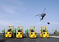 US Navy 050121-N-4166B-025 Sailors assigned to the Supply Department aboard USS Abraham Lincoln (CVN 72), line up on the flight deck with forklifts, awaiting supplies to be delivered by an MH-60S Knighthawk helicopter during a.jpg