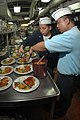 US Navy 050719-N-9551Z-127 Culinary Specialist 1st Class Rogelio Magpantay and Culinary Specialist 2nd Class Gomer Cubol prepare entrees for the executive officer dinner.jpg
