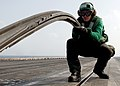 US Navy 060604-N-0119G-046 Aviation Boatswain's Mate Equipment Airman Wesley Maynard wraps one of four steam-powered catapults on the flight deck of the nuclear-powered aircraft carrier USS Enterprise (CVN 65).jpg