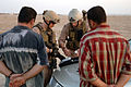 US Navy 070816-N-6794Z-006 Two Seabees attached to Explosive Ordnance Disposal Mobile Unit (EODMU) 11, Company 9-13, test the hands of two Iraqi men for the presence of explosives after the Sailors discovered two separate impro.jpg